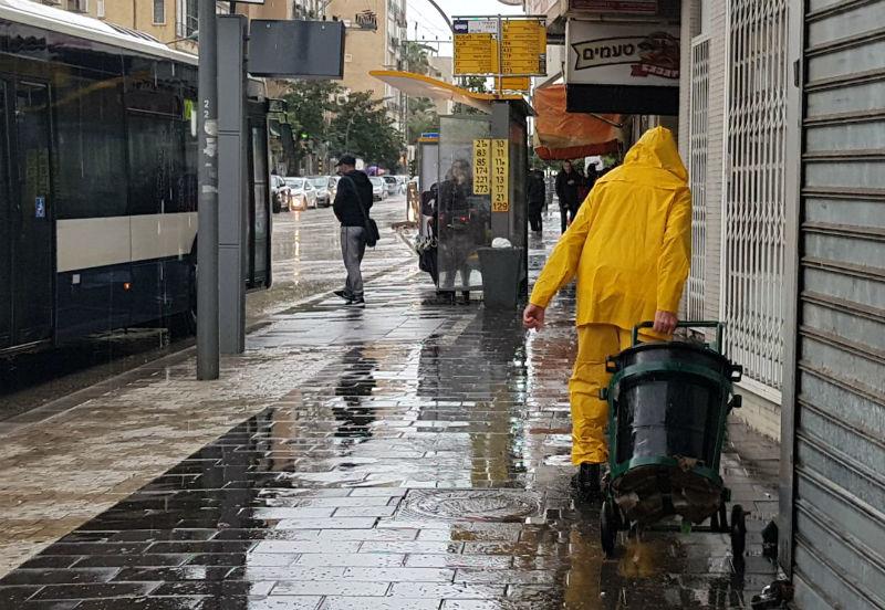 עובד נקיון מנקה את הרחובות בגשם