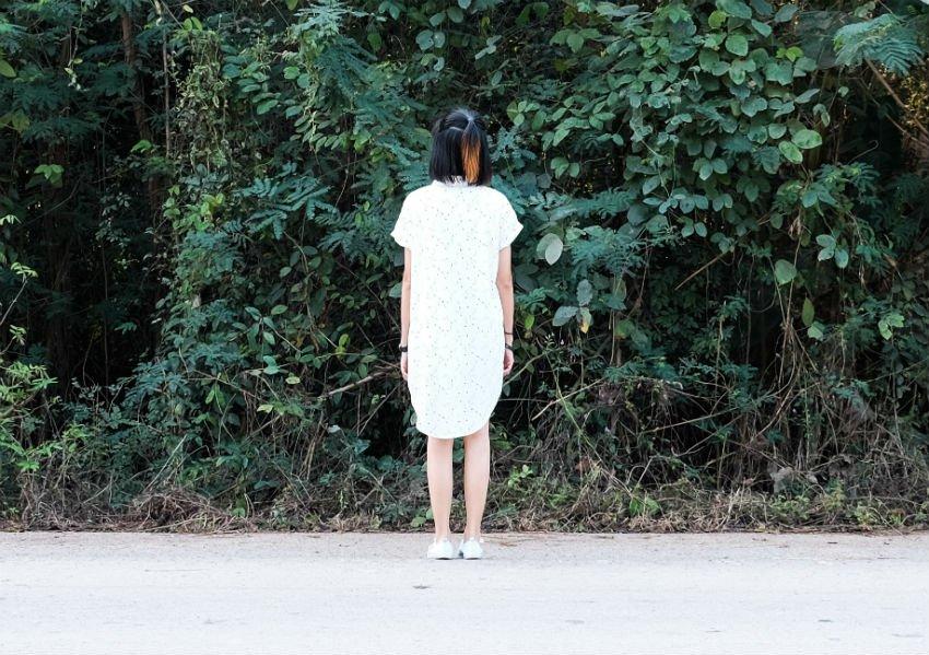 נערה בחורה אישה עומדת מול גינה גן